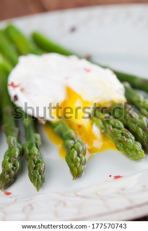 Green asparagus with poached egg on a plate - stock photo
