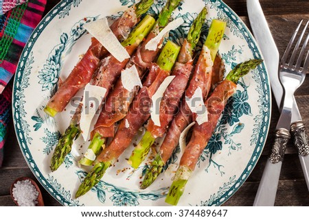 Green asparagus wrapped in parma ham on plate, rustic wooden background, top view - stock photo