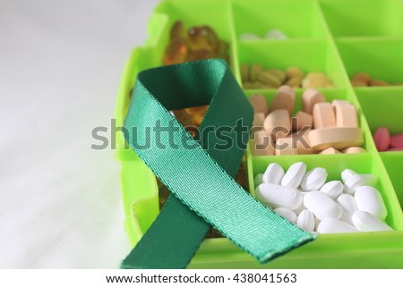 Green awareness cancer ribbon with medicine box  isolated on a white background - stock photo