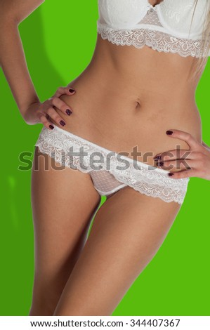 Green background Chroma. body skin.  Girl in white panties. young woman body with cotton panties  - stock photo