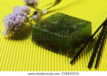 green bar soap with flower and aroma sticks on yellow background - stock photo
