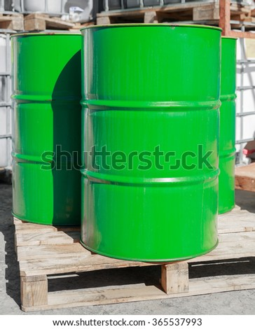 Green barrels standing on wooden pallets on a chemical plant - stock photo