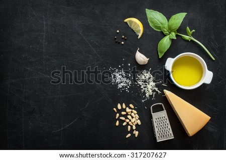 Green basil pesto - italian recipe ingredients on black chalkboard background from above. Parmesan cheese, basil leaves, pine nuts, olive oil, garlic, salt and pepper. Layout with free text space. - stock photo