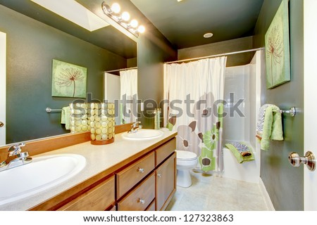Green bathroom with wood cabinet and shower tub. - stock photo