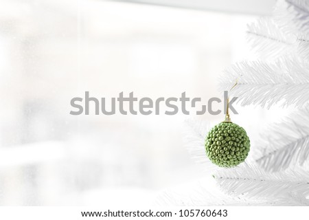 Green bauble hanging on white Christmas Three with winter scene behind the window - stock photo