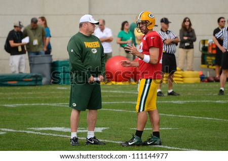 GREEN BAY, WI - AUGUST 19 : Green Bay Packers Quarterback Aaron Rodgers Talks with Head Coach Mike McCarthy During Training Camp Practice on August 19, 2012 in Green Bay, WI - stock photo