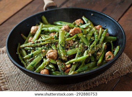 Green beans fried with chicken meatballs and garlic Asian style - stock photo