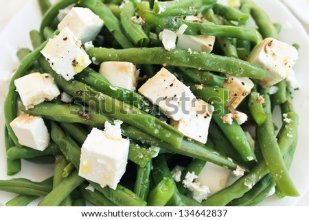Green beans salad with feta on a white plate - stock photo