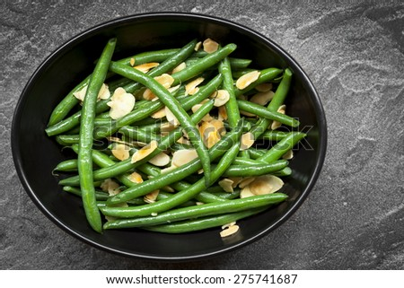 Green beans with toasted almonds, in black bowl over dark slate.  Overhead view. - stock photo