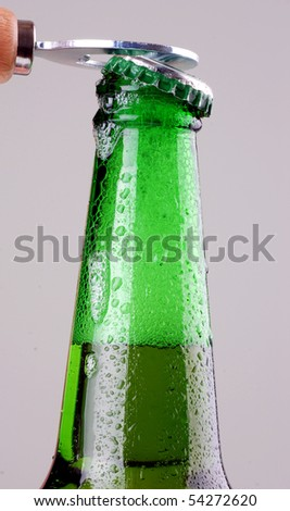 Green beer bottle being opened - stock photo