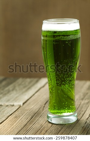 Green beer in glass for st. Patricks day on vintage background with toning - stock photo