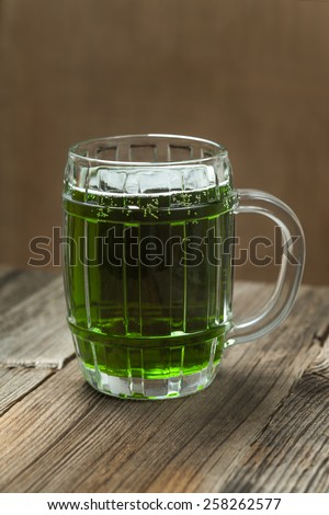 Green beer in glass for st. Patricks day on vintage wooden background - stock photo