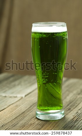 Green beer in glass for st. Patricks day on vintage wooden background with toning - stock photo