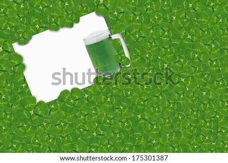 green beer in mug in shamrocks - stock photo