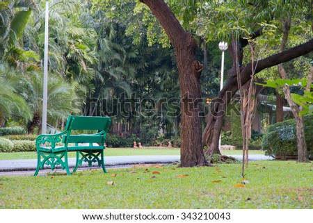 Green benches beside walkway in the park. - stock photo