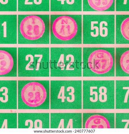 Green bingo card being used (white chips) - stock photo