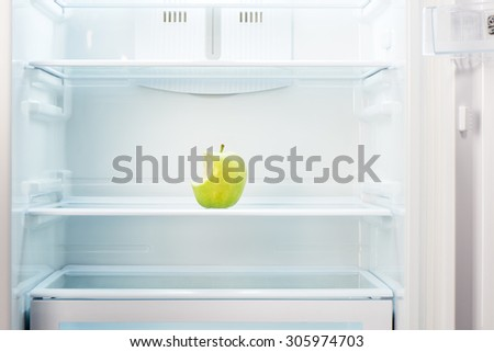 Green bitten apple on shelf of open empty refrigerator. Weight loss diet concept. - stock photo