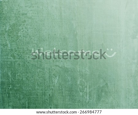 """Green blackboard texture background with text """"  Welcome """" and smiley face (light source from upper right hand corner  - stock photo"""
