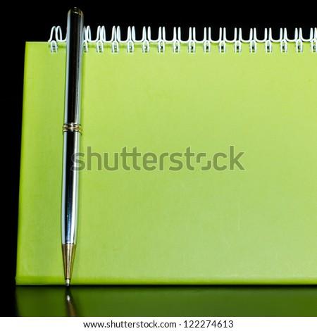 Green blank calendar organizer with pen - stock photo