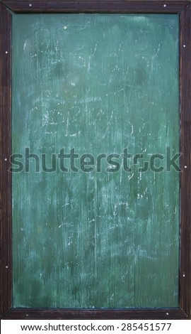 Green blank chalkboard with wooden frame and traces of chalk writing - stock photo