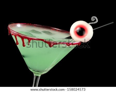 Green bloody Halloween cocktail with eye, close up - stock photo