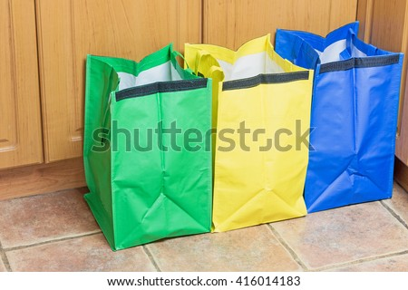 Green, blue and yellow bags are ready to use in sorting household waste - stock photo