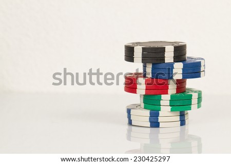 Green, Blue, Red and Black Playing Poker Chips Tower in Reflective White Background - stock photo