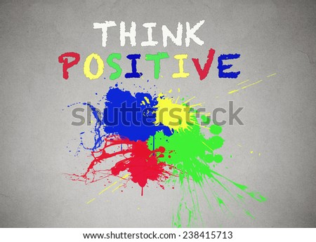 Green, blue, red, yellow splatter of paint isolated on grey wall background, blackboard with colorful splashes and think positive writing, words on it. Positive life concept. - stock photo