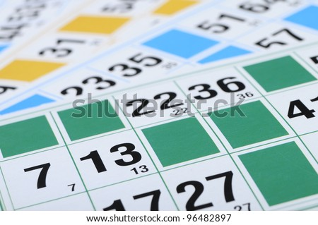 Green, blue, yellow bingo cards with focus on number thirteen - stock photo