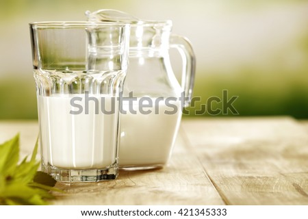 green blurred background and milk and leaves  - stock photo