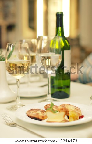 Green bottle of wine and two glasses with champagne and water also with dish anf fork on table in restaurant - stock photo