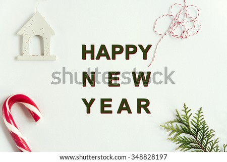 green branches and amazing christmas toys and sweets on white background, happy new year text - stock photo
