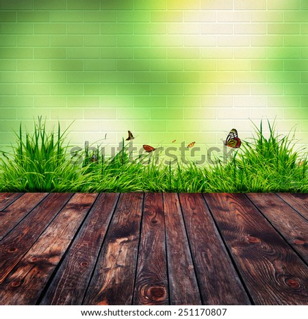 Green brick wall and green grass on wood floor - stock photo