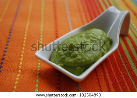 Green broad beans cream with basil in white china dish on orange fabric background - stock photo