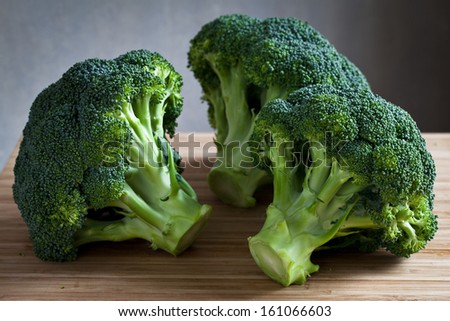 green broccoli on wooden board - stock photo