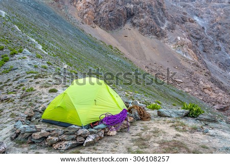 Green camping tent in mountains. Carefully constructed boundary stone wind protection wall and tent inside with rope and other climbing gear mountain landscape background - stock photo