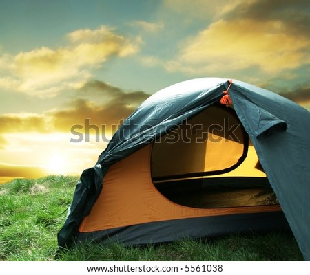 Green camping  tent on sunny grassland - stock photo