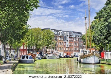 Green canal with moored yachts and apartment buildings, Gouda, The Netherlands. - stock photo