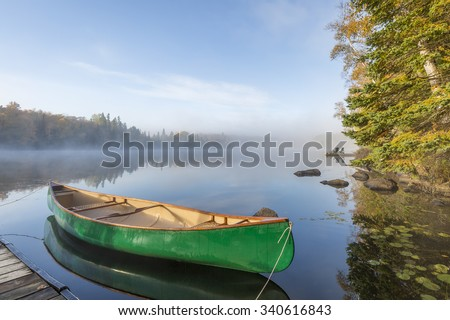 Green Canoe Tied to Dock on a Lake in Autumn - Ontario, Canada - stock photo