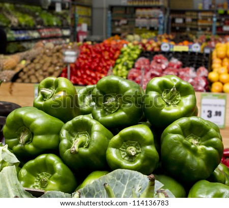 Green capsicum displayed for sale in vegetable shop - stock photo