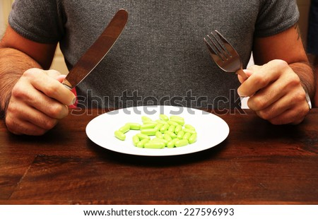 Green capsules on a plate as food supplement - stock photo