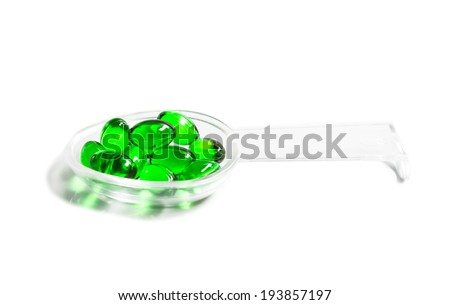 green capsules on a teaspoon isolated on white background - stock photo