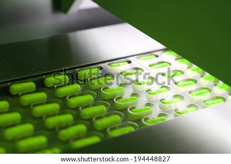 Green capsules packed in tablet packing machine - stock photo