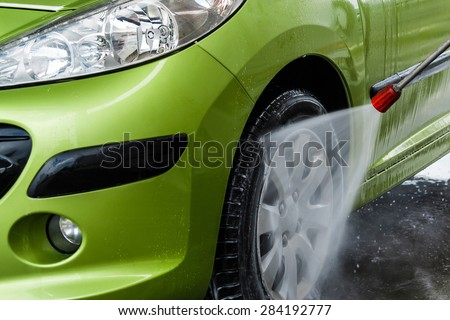 Green car in a hand car wash - stock photo
