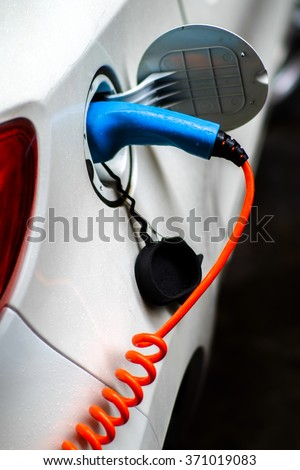 Green car is charging on its voltage supplier. - stock photo
