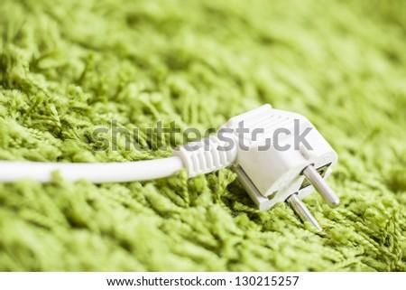 Green carpet on Power Plug Saving energy - stock photo