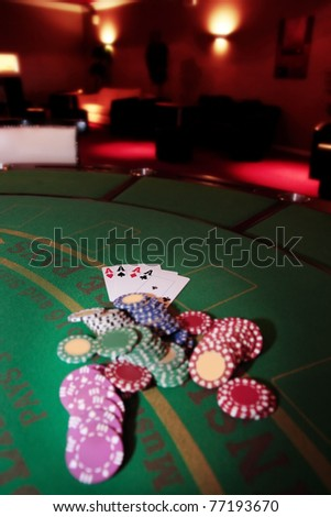 green casino table four aces in a poker game and a big pile of chips - stock photo