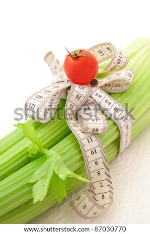 Green celery with tomato and tape measure, concept of healthy food and diet - stock photo