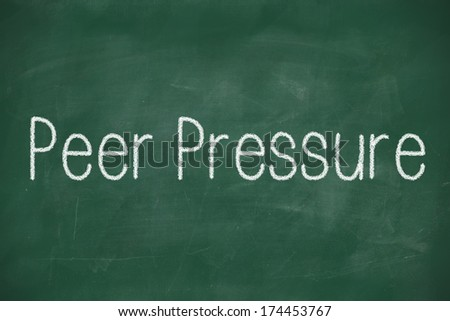 Green chalk board with the white words peer pressure written on it. - stock photo