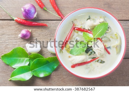 Green chicken curry with raw spicy ingredient Thai traditional food on brown wooden background - stock photo